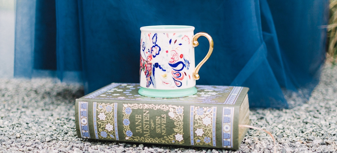 Now booking manuscript editing for Oct. - Dec. 2019 [Image: A Jane Austen novel on the ground with a gilded coffee mug on top. Foliage and a long blue skirt in the background.]