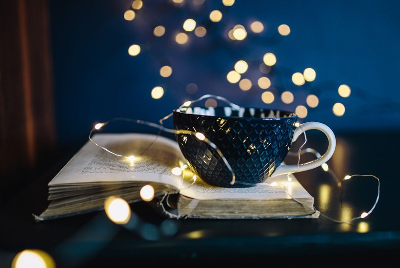 Book, tea cup, and fairy lights