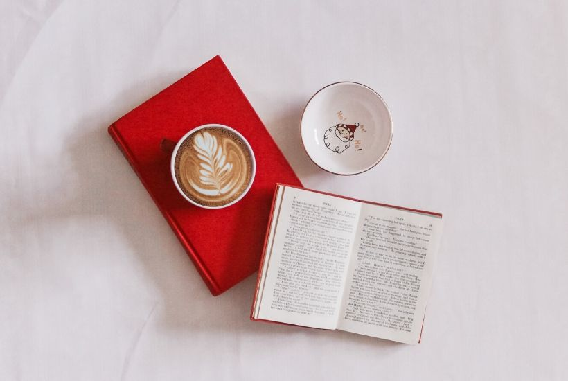 Coffee mug on red book with open Jane Austen novel and Santa dish
