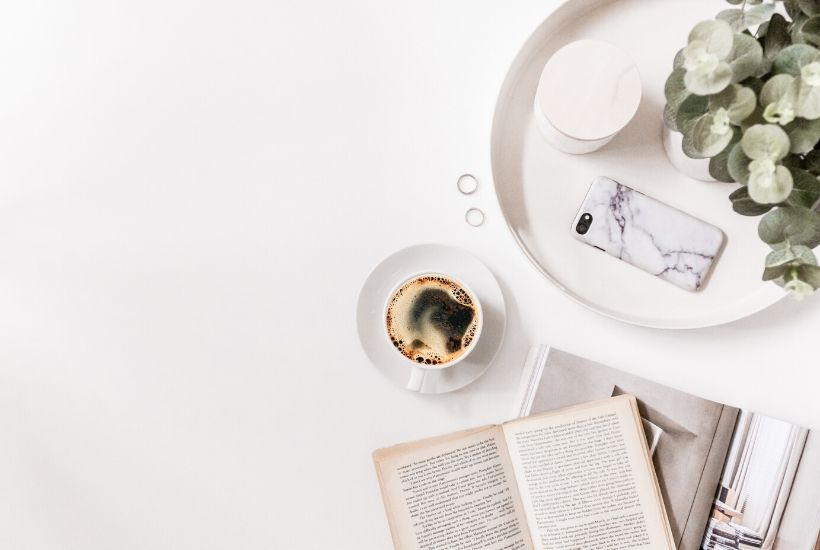 Five Elements of Story | Between the Lines Editorial | photo shows a cup of coffee, an open book, and a tray with eucalyptus and a cell phone