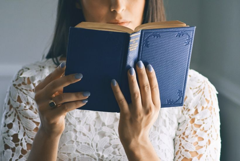 A woman wearing a white shirt is reading from a blue book