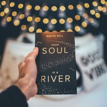 A person holds Your Soul is a River by Nikita Gill in front of the camera. There are blurred out lights and a bed in the background.