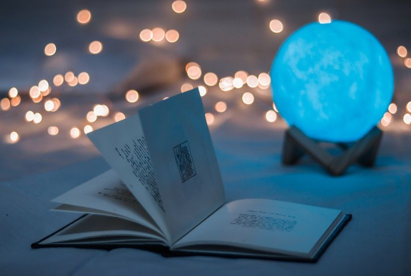 An open book, string lights, and glowing moon | Developing Your Magic System by Between the Lines Editorial
