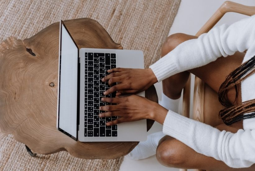 The Crossover Between New Adult and Young Adult in Fiction  (Image shows a person typing on their laptop)