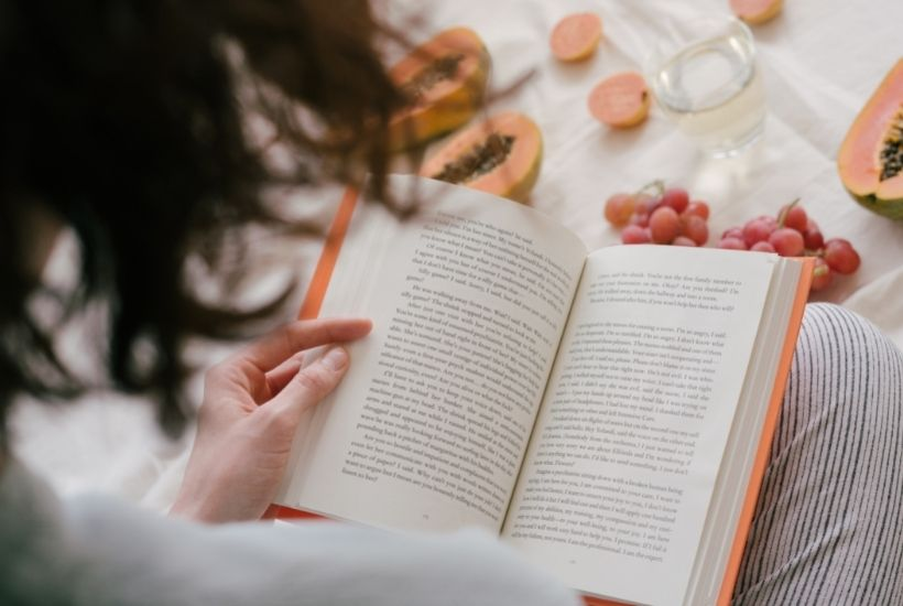 Camera looks over a person's shoulder to show them reading a book. There is fruit and a cup of water as well.