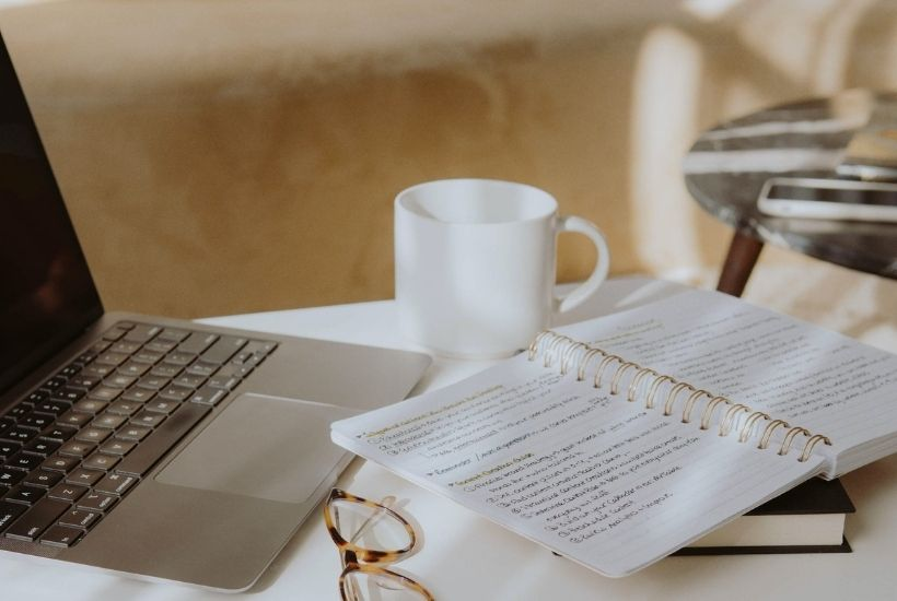 Popular writing advice you can ignore | laptop, coffee cup, glasses, and notebook on a coffee table | photo via Unsplash